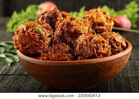 Spicy and crispy fried onion fritters.on a wooden background.Indian cuisine, stock photo