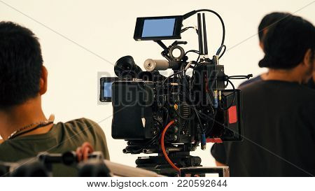 Behind the video shooting production crew team working and set of full hd camera equipment in studio. stock photo