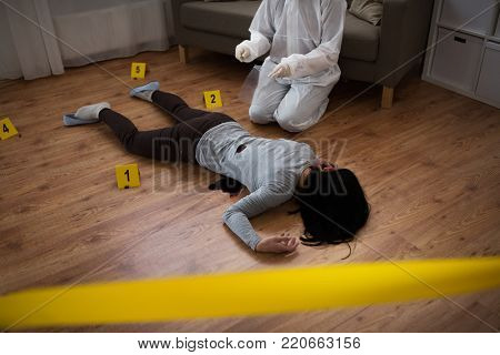 investigation and forensic examination concept - criminalist collecting evidence of murder of woman at crime scene fenced by police tape (staged photo) stock photo