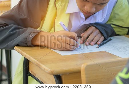 Asian boy student studying stressed headaches for test or exams in classroom, learning lessons doing final exam at high school with Thailand uniform in class room. Education system concept. stock photo