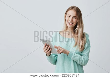 Portrait of happy young blonde business woman in casual clothes using tablet pc isolated against gray background. Smiling pretty girl holding a digital tablet computer. Modern technologies and business