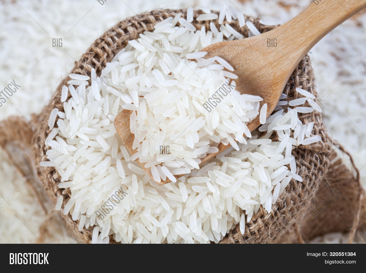 Close Up The Rice On Wood Spoon Put On The Rice Sack With Blurry Of Pile Rice