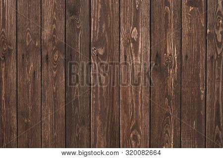 Old shabby wooden fence. Abstract pattern texture background. Brown faded boards. Oak bars, logs. Wood surface. Vertical stripes timber slats. Parallel bars. stock photo
