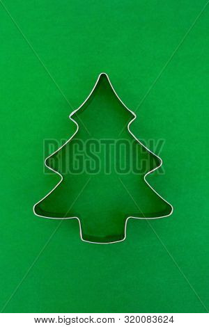 Cake forms for Christmas baking on green background. Tin form for gingerbread cookies. Form baking christmas tree closeup. stock photo