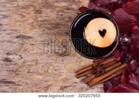 Autumn mulled wine or gluhwein based on red wine with  apple and spices cinnamon sticks on  wooden background. Seasonal beverages recipe. autumn mood, inspiration. Autumn hot drink Top view. stock photo