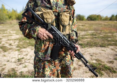 Soldier holds a machine gun in his hands, close-up. Military in green camouflage on the battlefield with a black rifle stock photo