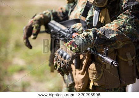A soldier in gloves and green camouflage holds in hands a machine gun that hangs on his neck. AK47 assault rifle close-up stock photo