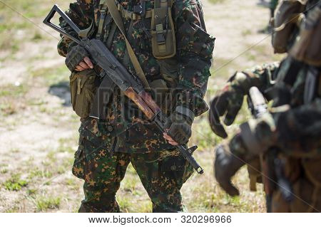 Close-up of two military men in green camouflage. Defensive unit. Soldiers hold AK47 machine guns in hands. stock photo