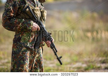 Soldier holds a rifle in his hands, close-up. Military in green camouflage on the battlefield with a black machine gun stock photo