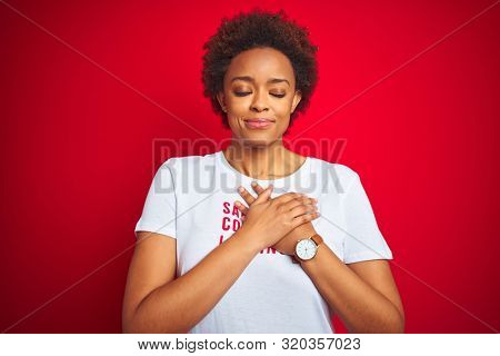 African american woman wearing sarcastic comments t-shirt over red isolated background smiling with hands on chest with closed eyes and grateful gesture on face. Health concept. stock photo