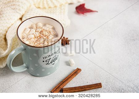 Hot cocoa mug with murshmallows, autumn leaves, anise stars on grey background. Close up, copy space. Fall, Thanksgiving, greeting card concept. Cozy autumn stock photo