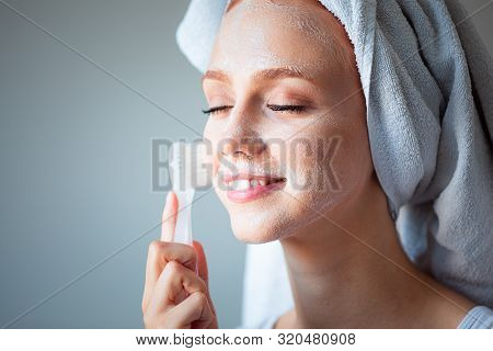Cute red hair young woman gently shaving armpit epilation hair removal with ergonomic pink shaver. Body care skincare beauty concept stock photo