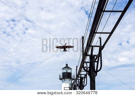 St Joseph outer lighthouse with Cormorant flying and catwalk stock photo