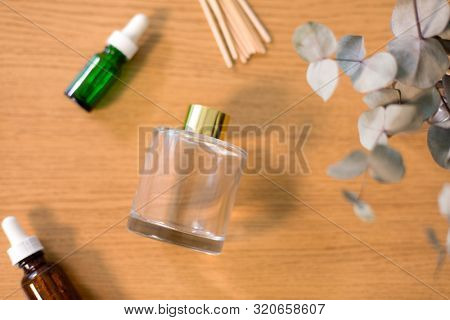 home perfume and aromatherapy concept - aroma reed diffuser, essential oil and branches of eucalyptus populus on wooden table stock photo
