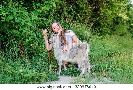 Girl play cute goat. Feeding animal. Protect animals. Veterinarian occupation. Eco farm. Love and care. Animals law. Woman and small goat green grass. Farm and farming concept. Village animals stock photo