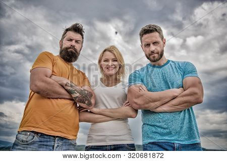 Strength in unity. Woman and men look confident sky background. Threesome stand confidently with folded arms. Threesome look down at you. Behaviors of cohesive team. Ways to build ohesive team stock photo