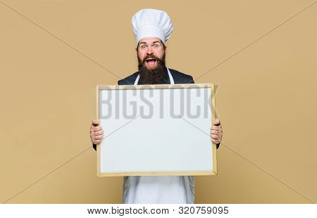 Master cook giving cooking class. Bearded man cook or chef holds empty board in cooking school. Chef teaching master class. Handsome cook holds blank board. Place for text. Restaurant or cafe menu stock photo