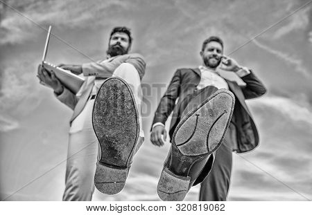 Businessmen making step bottom view. Business technologies coming. Big step for entrepreneurship. Smashing competitiveness. Business partner busy with phone call moving forward, foot shoe close up stock photo