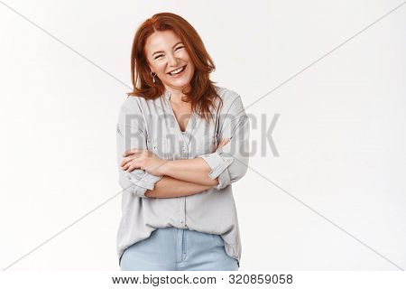 Beauty not care age. Attractive cheerful redhead middle-aged redhead woman laughing joyfully feel happiness positive emotions giggling funny entertaining conversation, cross arms chest relaxed stock photo