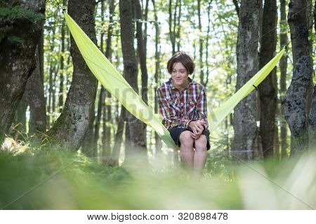Happy boy on yellow hammock in spring forest. Travel landscape concept. Outdoor camping