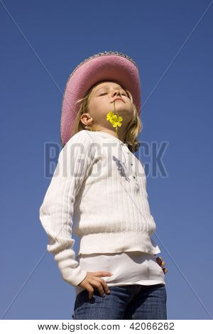 A young girl with hat and a flower in her mouth soaking up the sun. Closed eyes. Isolated on blue background. stock photo
