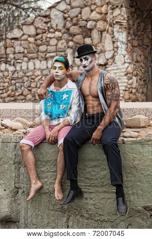 Handsome comedia del arte male performers sitting outside stock photo