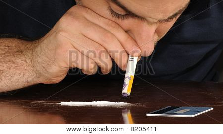 A man snorting cocaine with a 50 NIS bill after creating the line with a credit card stock photo