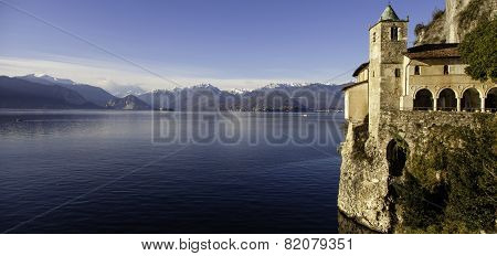 Panorama of the Hermitage of Santa Margherita del Sasso, an ancient cloistered monastery located on the shores of Lake Maggiore in Lombardy. In the background, the snow-capped peaks of the Swiss Alps. stock photo