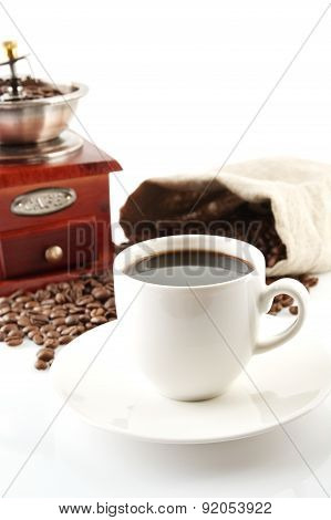 Coffee cup with winnower and sack of coffee beans on white