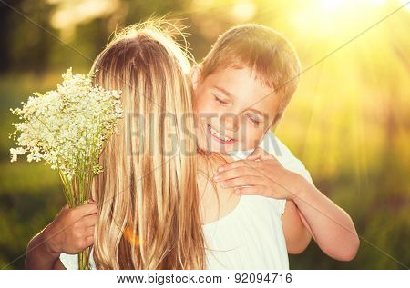 Mother and her little son with bouquet of flowers outdoors, Happy family mom and kid kissing and hug
