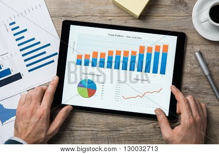 Top view of digital tablet with financial year overview on screen. Businessman analyzing investment