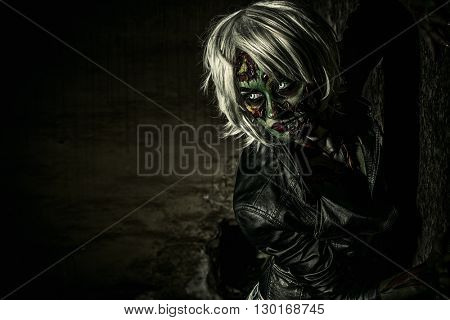 Terrible bloodthirsty zombie woman in the slums. Body-painting project. Glamorous zombie girl. Hallo