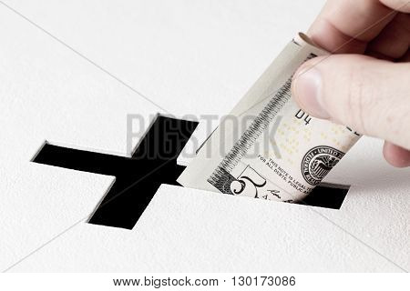 Hand of parishioner is inserting five dollars into hole for donations in form of Christian cross on white background. Idea of donations for church and good deeds