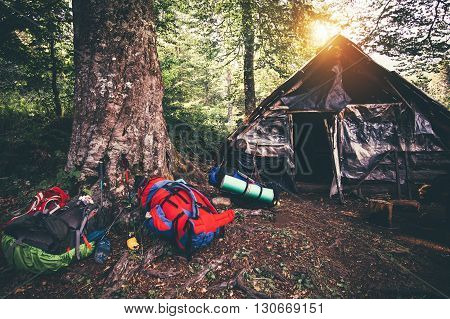 Backpacks and abandoned house camping outdoor Travel Lifestyle hiking equipment forest nature on background