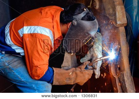 industrial welding being carried out on a mining site with safety clothing and equiupment in use stock photo