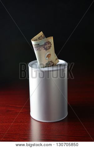 One thousand dirham note inserted in the saving can. Saving tin and UAE Dirham note. Stock photo. stock photo