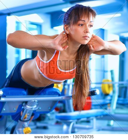 Sports young woman doing exercises on trainer back machine in the gym. stock photo