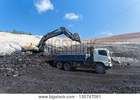 yellow backhoe work in coalmine under blue sky. stock photo