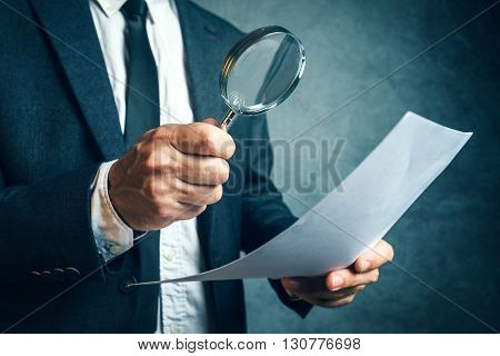 Tax inspector investigating financial documents through magnifying glass forensic accounting or financial forensics inspecting offshore company financial papers documents and reports.