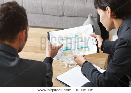 Business meeting at office. Youing businsspeople sitting on sofa, talking over financial charts. High angle view. stock photo