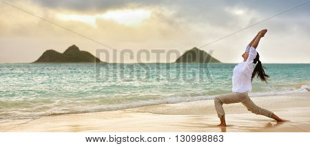 Yoga woman meditating in warrior I pose at hawaiian beach during beautiful morning sunrise against Lanikai mountains Hawaii landmark. Banner panoramic crop for advertisement. stock photo