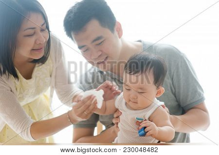 Mother wipes baby hand with tissue paper. Asian family spending quality time at home, living lifestyle indoors. stock photo