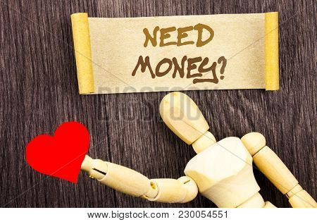 Text sign showing Need Money Question. Conceptual photo Economic Finance Crisis, Cash Loan Needed written Sticky Note Love Heart Holding By Sculpture the wooden background. stock photo