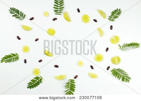 Pattern made of green lime, leaves and red beans. top view. stock photo