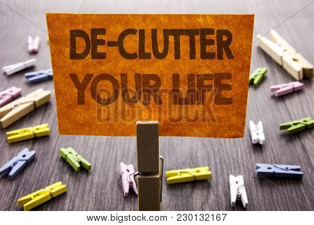 Handwritten text sign showing De-Clutter Your Life. Business concept for Free Less Chaos Fresh Clean Routine written sticky Note the wooden background. stock photo