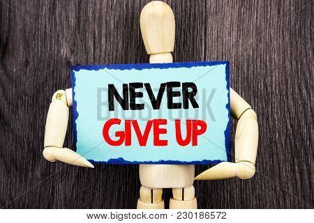 Writing text showing  Never Give Up. Concept meaning Motivation Quote For Success Achievement Challenge written Sticky Note Holding By Sculpture the wooden background. stock photo