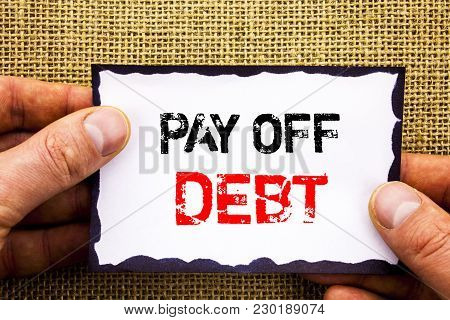Writing text showing  Pay Off Debt. Concept meaning Reminder To Paying Owed Financial Credit Loan Bills written Sticky Note Paper Holding Hand with Finger. stock photo