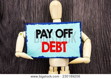 Writing text showing  Pay Off Debt. Concept meaning Reminder To Paying Owed Financial Credit Loan Bills written Sticky Note Holding By Sculpture the wooden background. stock photo