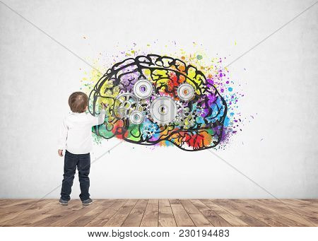 Rear view of a cute little boy wearing a white shirt and dark blue jeans writing or drawing with a marker. A concrete wall background with a cog brain sketch on it. stock photo