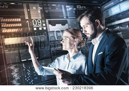 Team work. Clever experienced young programmer pointing to the screen of an amazing futuristic device while her calm experienced colleague standing next to her and looking at the tablet in his hands stock photo